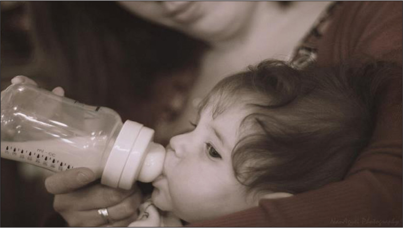 Baby drinking formula from a bottle. Photo © Nanagyei, with no modifications made, available here: https://www.flickr.com/photos/nanagyei/7150163611/sizes/z/ under the Creative Commons License.