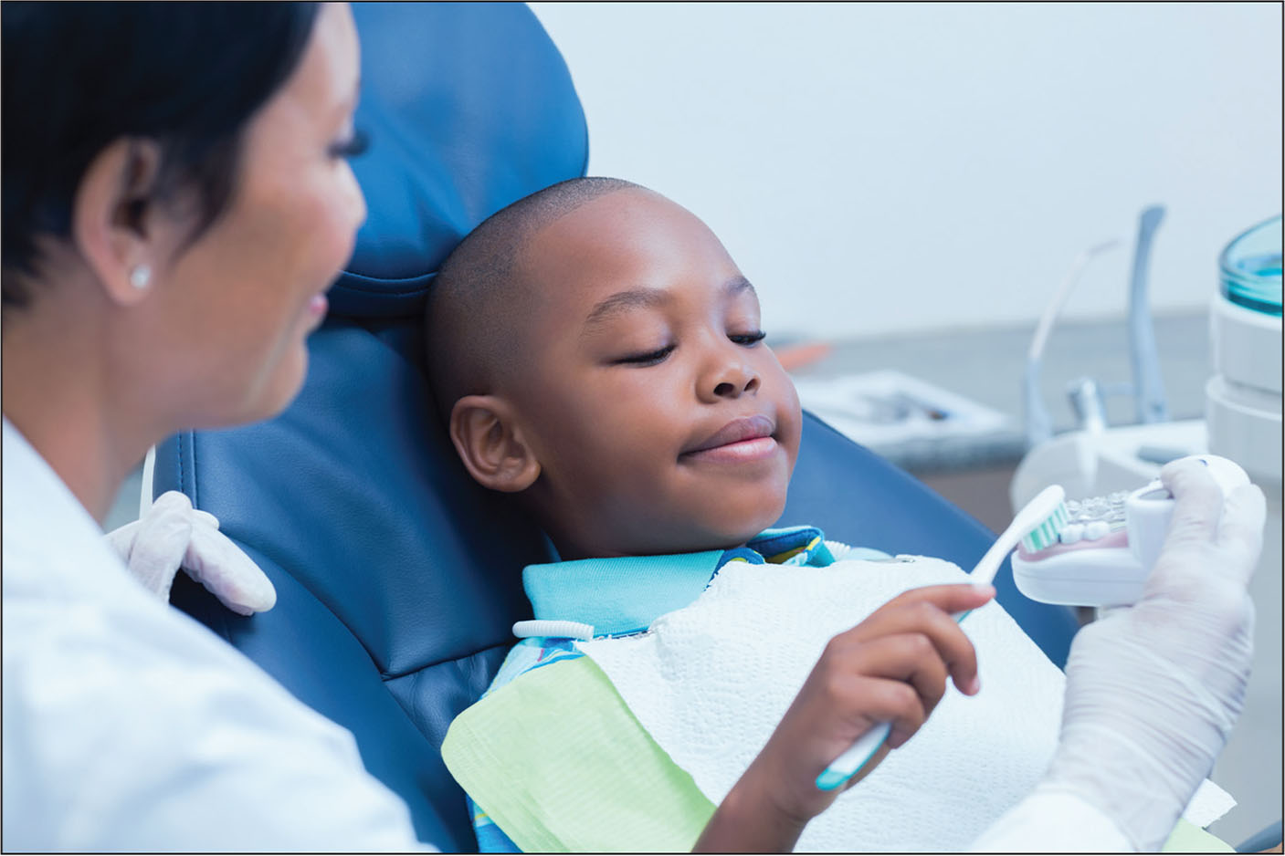 �A;A young boy practicing proper technique for teeth brushing with his dentist.�A;© Shutterstock