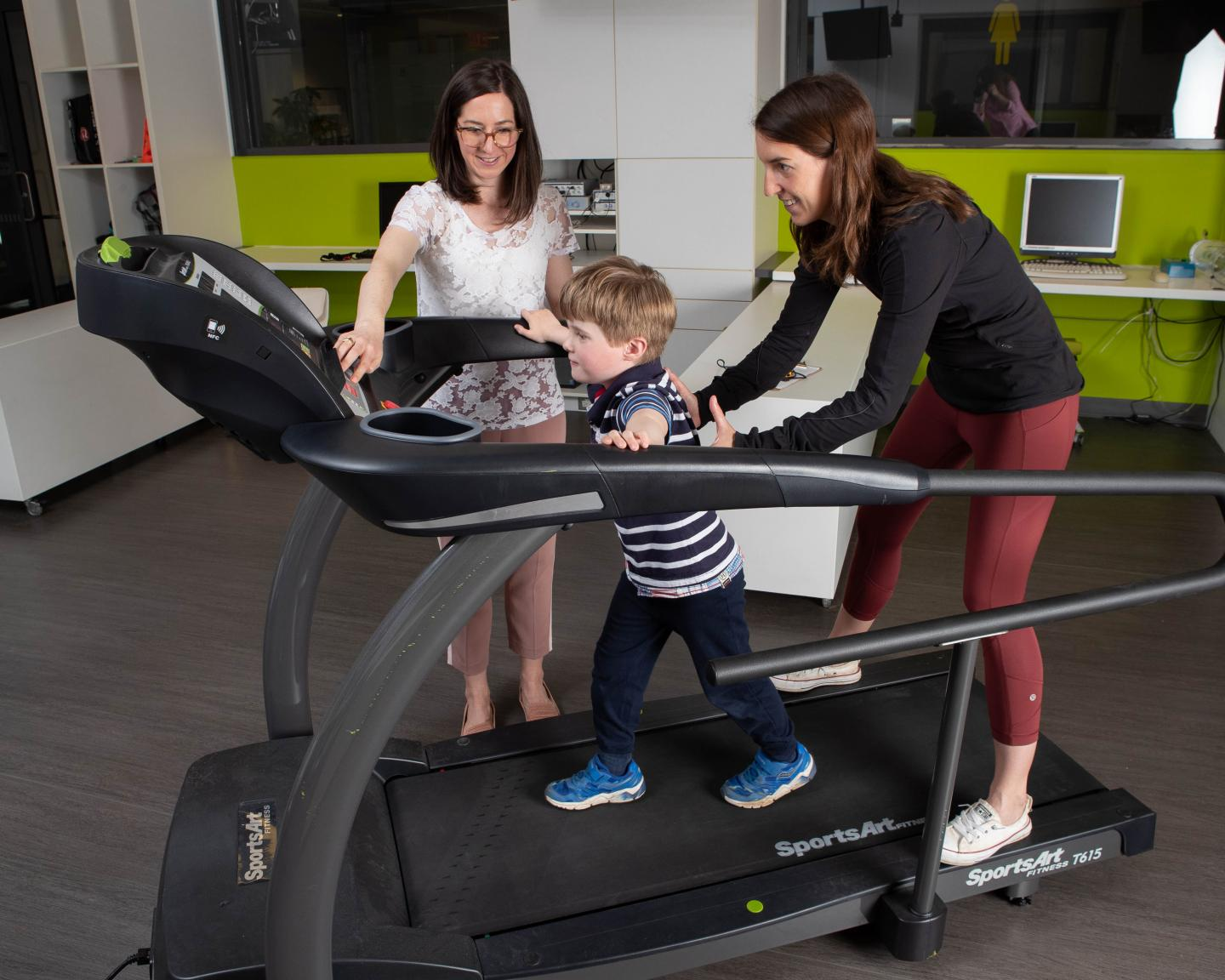 Photo of researchers with young boy on treadmill
