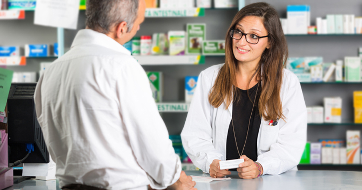 A photo of a pharmacist speaking with a customer