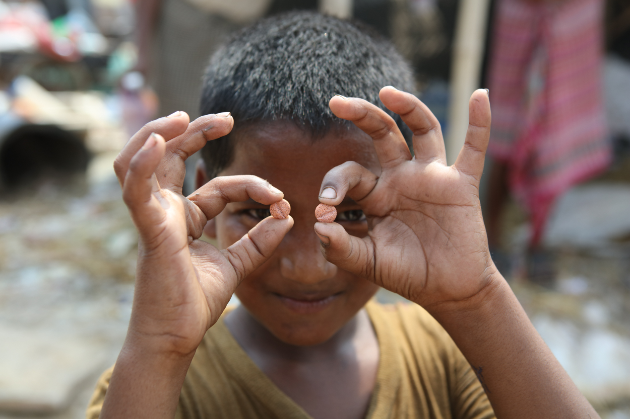 A boy in Delhi holds up improved TB medicines for children