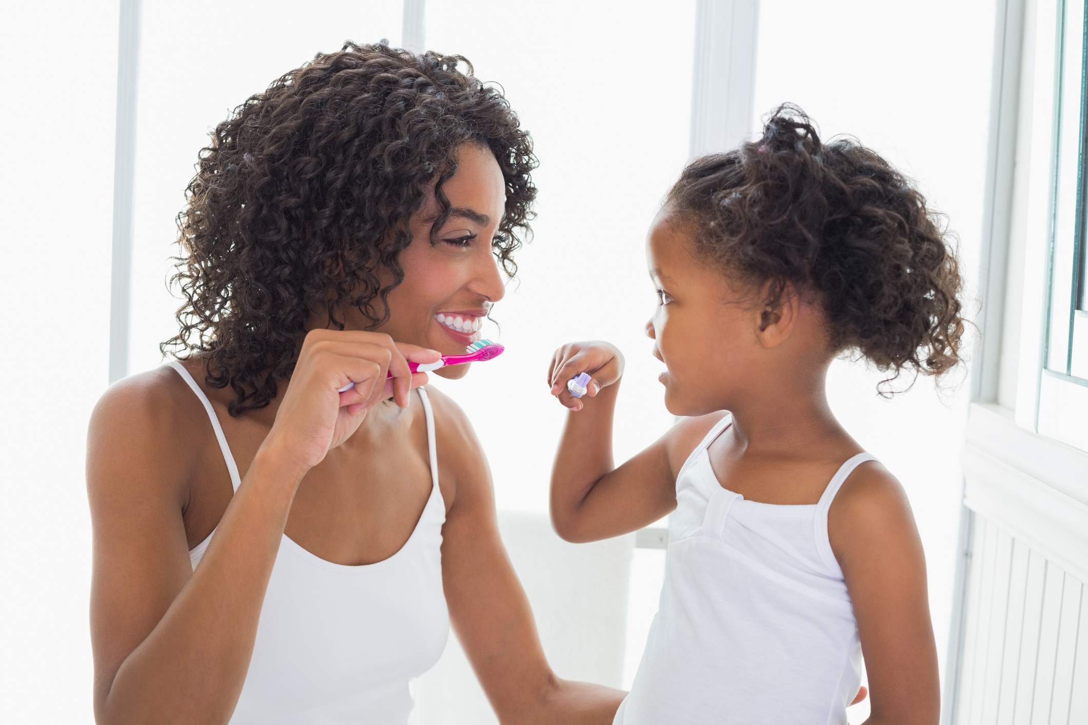 Child and mother brushing their teeth